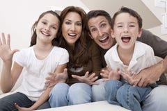Glückliche Familie, die Spaß-sitzendes zu Hause lachen hat Stockfotos