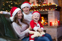 Glückliche Familie, die zu Hause auf Couch vor Kamin im festlichen Weihnachtsraum sitzt Stockfotos