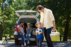 Glückliche Familie, die zur Autoreise fertig wird Stockfotos