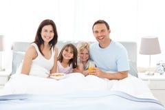 Glückliche Familie, die zusammen auf dem Bett frühstückt Stockbild