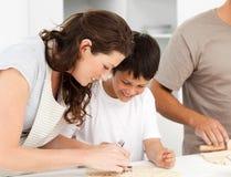 Glückliche Familie, die zusammen Biskuite kocht Lizenzfreie Stockfotografie