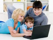 Glückliche Familie, die zusammen im Laptop schaut Stockfoto