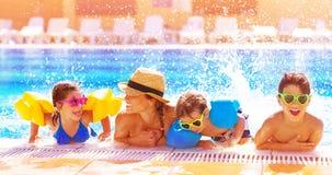 Glückliche Familie im Pool Stockfotos