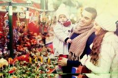 Glückliche Familie im Weihnachtsmarkt Stockbilder