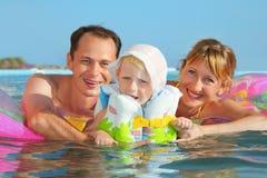 Glückliche Familie mit dem kleinen Mädchen, das im Pool badet Stockbild