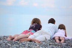 Glückliche Familie mit dem Mädchen, das auf dem Strand, zurück liegend liegt Stockfotos