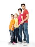 Glückliche Familie mit den Kindern, die zusammen in der Linie stehen Lizenzfreie Stockfotos