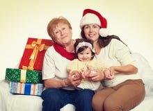 Glückliche Familie mit Kastengeschenk, Frau mit Kind und älteren Personen - Feiertagskonzept Stockbilder