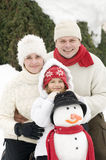 Glückliche Familie mit Schneemann Lizenzfreies Stockfoto