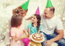 Glückliche Familie mit zwei Kindern in den Parteihüten zu Hause Stockbilder