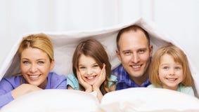 Glückliche Familie mit zwei Kindern unter Decke zu Hause Lizenzfreies Stockfoto