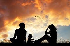 Glückliche Familie am Sonnenuntergang Stockbild