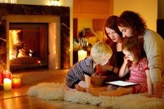 Glückliche Familie unter Verwendung eines Tabletten-PC durch einen Kamin Stockfoto