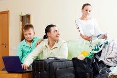 Glückliche Familie von zwei Erwachsenen und von Sohn, die Hotel auf dem Internierten aufheben Lizenzfreie Stockbilder