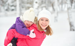 Glückliche Familienmutter und Babytochter, die im Winterschnee spielt und lacht Stockbild