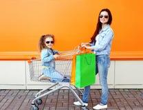 Glückliche Familienmutter und -kind mit Laufkatzenwarenkorb und -Einkaufstaschen Stockfoto