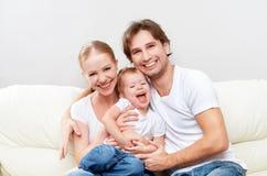 Glückliche Familienmutter, Vater, Kinderbabytochter zu Hause auf dem spielenden Sofa und Lachen Lizenzfreie Stockfotos
