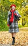 Glückliche fällige Frau, die in Herbst geht Lizenzfreies Stockbild