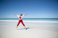 Glückliche fällige Frau am tropischen Strand Stockfotografie