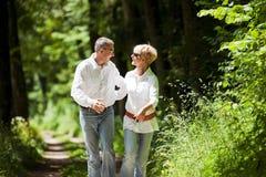Glückliche fällige Paare draußen Stockbild
