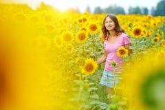 Glückliche Frau auf dem Sonnenblumegebiet Stockbild
