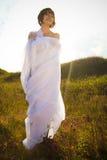 Glückliche Frau in den weißen Geweben in grünem im Freien Lizenzfreies Stockfoto