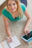Glückliche Frau, die auf dem Boden tut ihre Hausarbeit unter Verwendung der Tablette liegt Stockbild