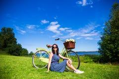 Glückliche Frau, die auf dem Gras mit Weinlesefahrrad auf dem Meer sitzt Stockfoto