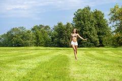 Glückliche Frau, die auf Sommer- oder Frühlingsrasenfläche läuft Stockfotografie
