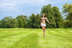 Glückliche Frau, die auf Sommer- oder Frühlingsrasenfläche läuft Stockbild