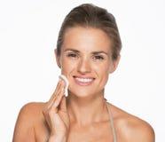 Glückliche Frau, die Baumwollauflage verwendet, um Make-up zu entfernen Stockfotografie