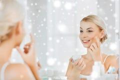 Glückliche Frau, die Creme am Gesicht am Badezimmer aufträgt Stockfotos
