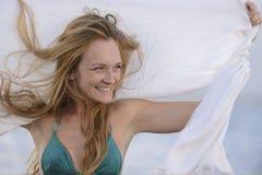 Glückliche Frau, die dem Wind auf dem Strand glaubt Stockfotos