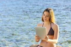 Glückliche Frau, die einen Tablettenleser auf der Strandküste liest Stockbild