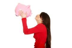 Glückliche Frau, die ihr Sparschwein küsst Lizenzfreie Stockbilder