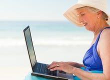 Glückliche Frau, die an ihrem Laptop am Strand arbeitet Stockfoto