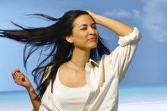 Glückliche Frau, die im Sommerwind steht Stockfotos