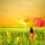Glückliche Frau, die roten Regenschirm und Sonnenuntergang anhält Stockfotografie