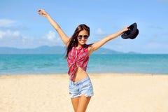 glückliche Frau, die am Strand an einem sonnigen Tag lächelt Lizenzfreies Stockfoto
