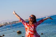 glückliche Frau, die am Strand an einem sonnigen Tag lächelt Stockbild