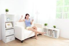 Glückliche Frau, die Tabletten-PC auf Sofa verwendet Stockbild