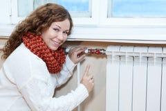 Glückliche Frau, die wenn Thermostat auf Zentralheizungsheizkörper gestikuliert, gesteuert wird Stockfotos
