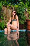 Glückliche Frau im Bikini, der nahe Swimmingpool sitzt Stockbild