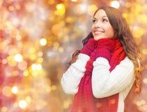 Glückliche Frau im Schal und in den Handschuhen über Lichtern Lizenzfreies Stockbild