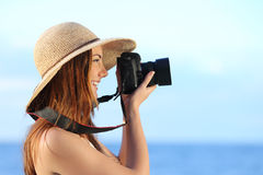 Glückliche Frau im Urlaub, die mit einer dslr Kamera fotografiert Lizenzfreie Stockbilder
