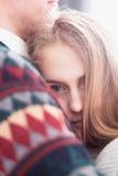 Glückliche Frau kleidete im Pullover setzte ihren Kopf auf Schulter des Mannes an Stockfoto
