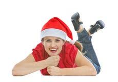 Glückliche Frau mit dem Weihnachtshut, der auf Fußboden legt Lizenzfreie Stockbilder