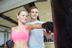 Glückliche Frau mit persönlichem Trainerverpacken in der Turnhalle Stockbilder
