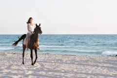 Glückliche Frau mit Pferd auf Seehintergrund Lizenzfreies Stockfoto