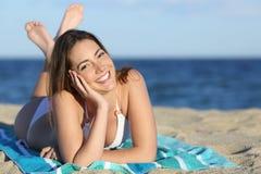 Glückliche Frau mit weißem vervollkommnen das Lächeln, das auf dem Strand stillsteht Stockbild